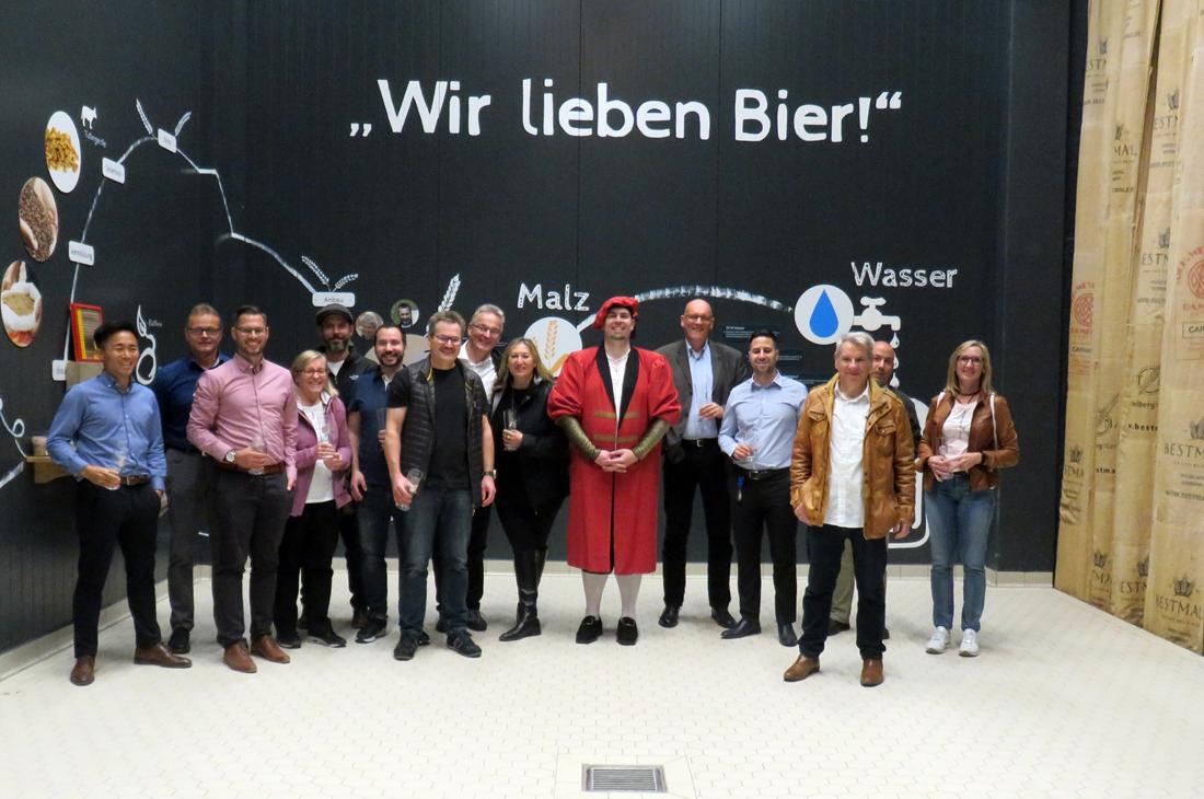 """Gruppenbild von Jens Caspary und Team mit Magier """"Thorstein Gerstentreiber"""" vor einem Glaabsbräu-Plakat."""