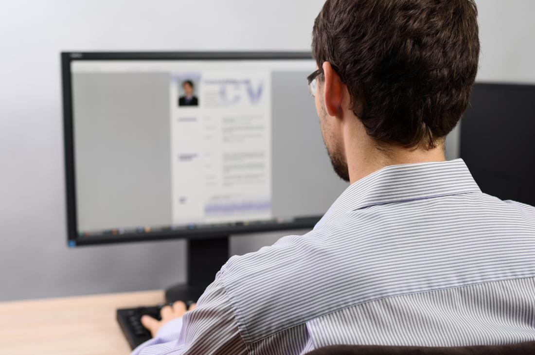 Junger Mann sitzt vor dem Computer und schreibt an seinem Lebenslauf.