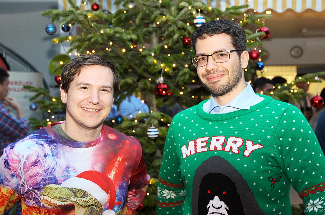Zwei Mitarbeiter in festlichen Weihnachtspullovern.