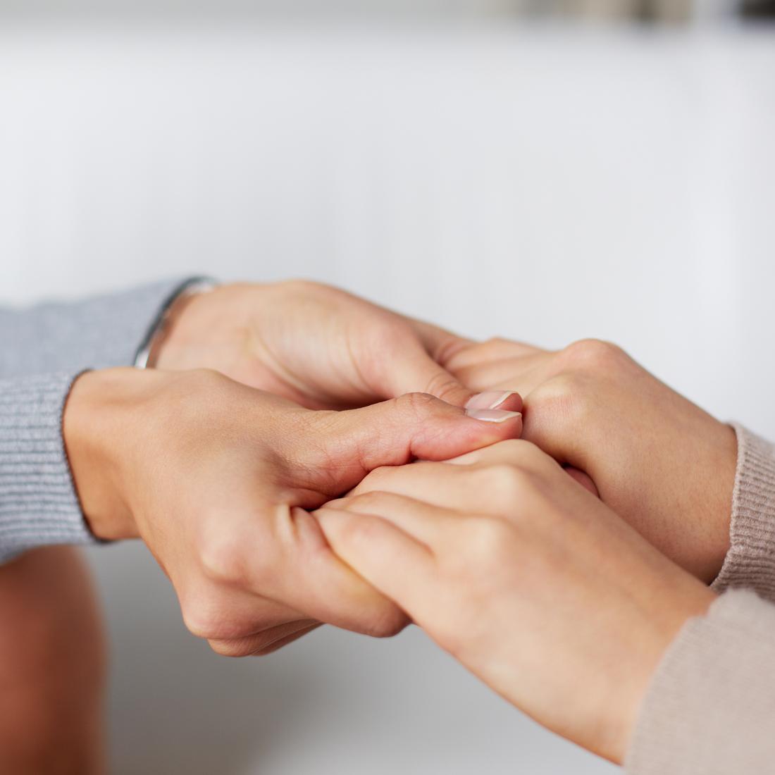 Foto von zwei Paar Händen, die einander halten.