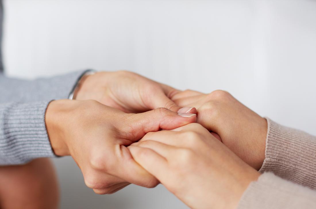 Fotovon zwei Paar Händen, die einander halten.