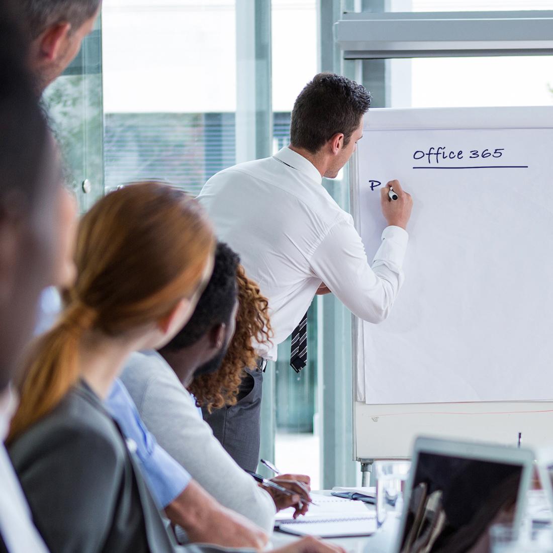 Ein Mann steht vor einem Flipchart im Büro und erklärt Leuten etwas zu Office 365.
