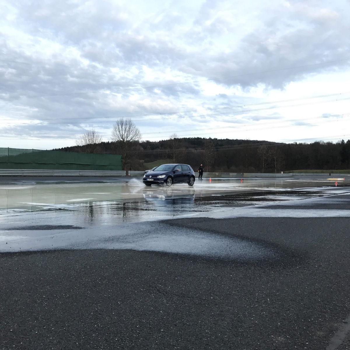 Ein Auto faehrt waehrend eines Fahrischerheitstrainings auf einer nassen Straße.