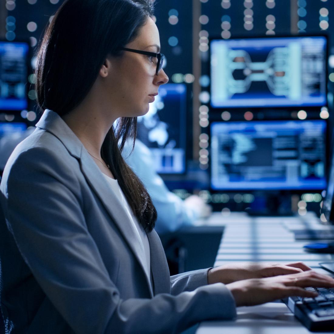 Junge Frau sitzt vor einem Desktop und wertet Daten aus.