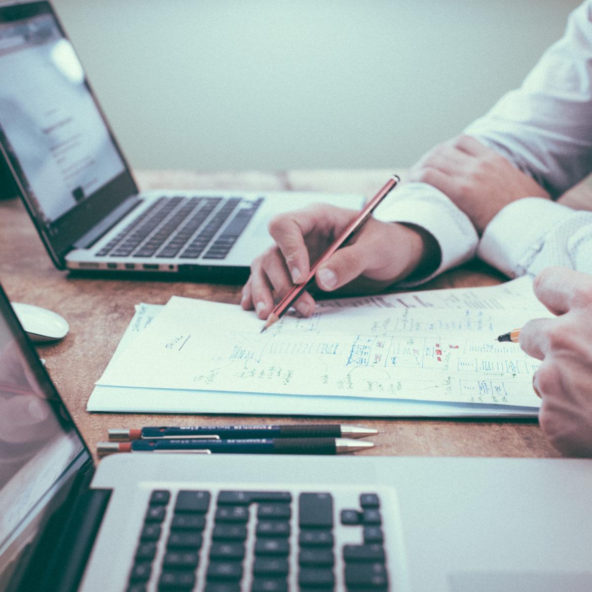 Business Männer sitzen vor zwei Laptops und fertigen Notizen auf einem Blatt an