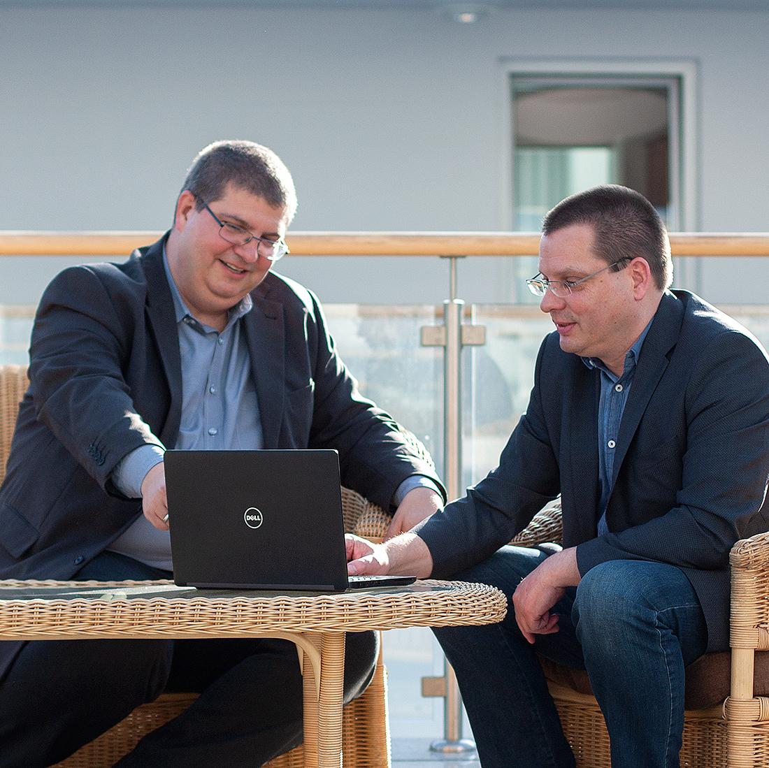 Arne Palow (l.) und Joerg Dubslaff (r.), Mitarbeiter von Controlware Berlin, sitzen vor einem Laptop bei einer Besprechung.
