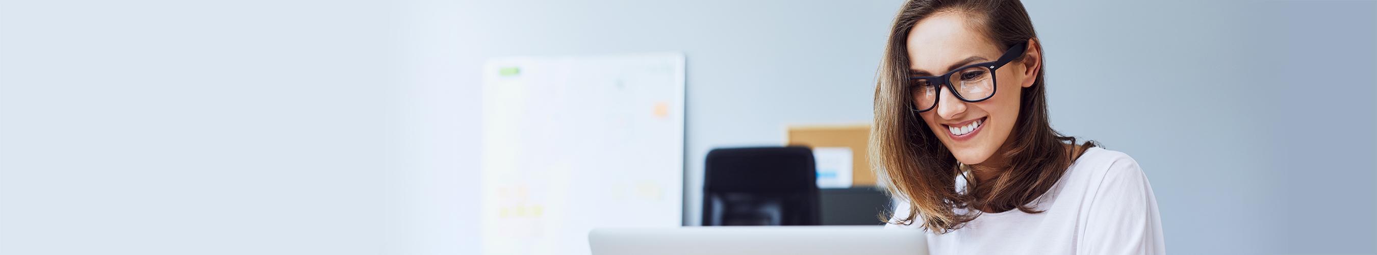 Junge Frau mit brille sitzt vor Laptop; Bild zum Job des Monats als Enterprise Architekt