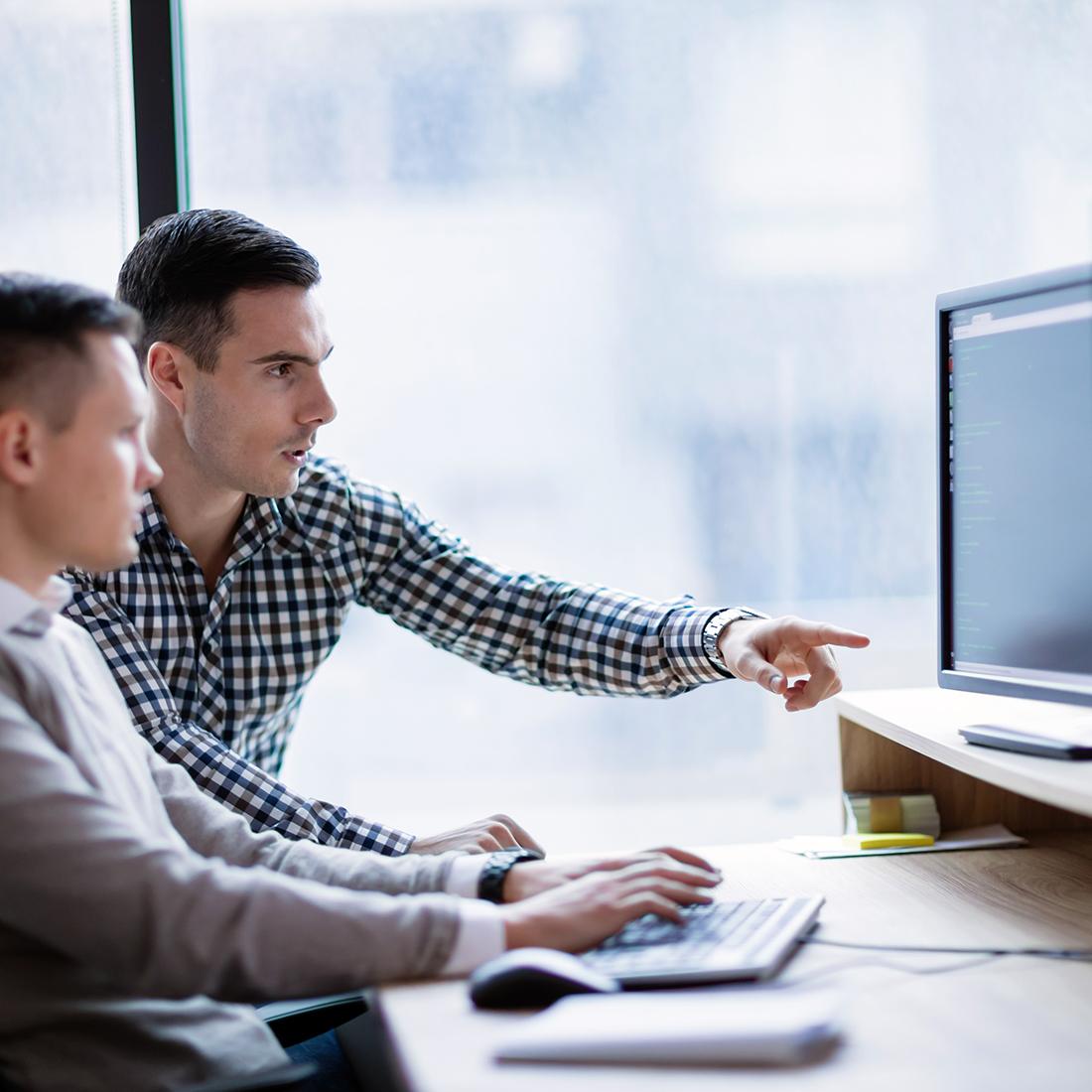 zwei maenner sitzen vor zwei bildschirmen, bild zur illustration des job des monats als security consultant schwachstellenmanagement penetration testing